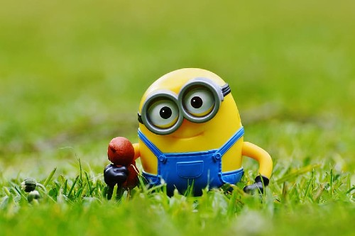 Minion toy stood in the grass with head tilted