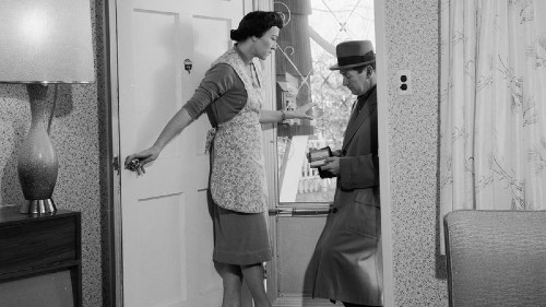 black and white picture of a salesman at a womans door in the 40s